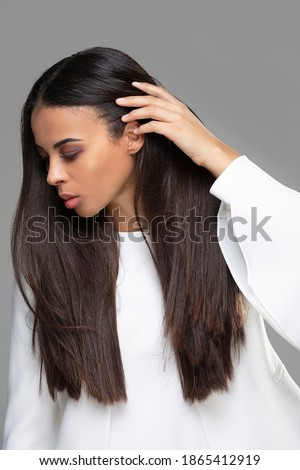 Beauty African Ethnic female with long straight hair and glamour makeup. Closeup face photo of attractive elegant woman. Studio shot. Royalty-Free Stock Photo #1865412919