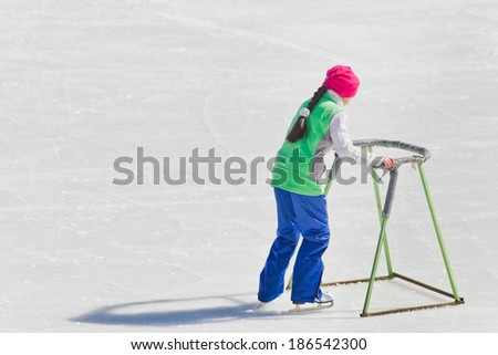 Adorable little girl in winter clothes and hat skating on ice rink at Medeo #186542300