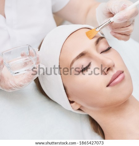 Cosmetology beauty procedure. Young woman skin care. Beautiful female person. Rejuvenation treatment. Facial chemical peel therapy. Clinical healthcare. Doctor hand. Dermatology cleanser. Royalty-Free Stock Photo #1865427073