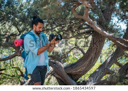 Male photographer with a camera on a hike. Young handsome guy with a backpack and a professional camera takes pictures of nature on a hike among the trees in the mountains