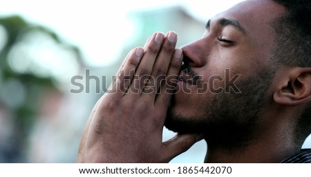 Spiritual young black African man praying to GOD. Person looking to sky with HOPE and FAITH Royalty-Free Stock Photo #1865442070
