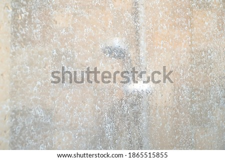 Blurred image of dry water hard stain of soap and shampoo on glass in the bathroom. Difficult to clean. Copy space. Royalty-Free Stock Photo #1865515855