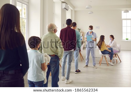 Diverse people lining up waiting for their turn to get shots at the hospital vaccination center. Young men and women, senior citizens and kids standing in queue for antiviral Covid-19 or flu vaccine Royalty-Free Stock Photo #1865562334