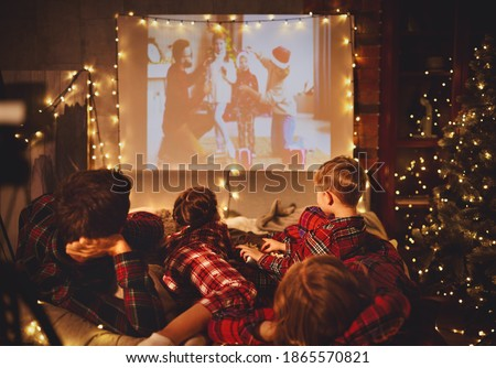 happy family in checkered pajamas: mother father and children watching projector, TV, movies with popcorn in christmas holiday evening   at home 