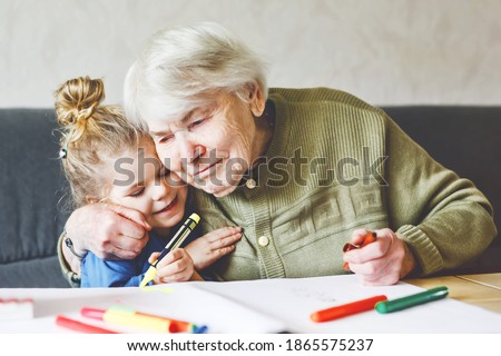Beautiful toddler girl and grand grandmother drawing together pictures with felt pens at home. Cute child and senior woman having fun together. Happy family indoors