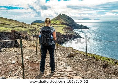 Girl hiking rocky cliffs clear near water of Atlantic Ocean bay Ponta de Sao Lourenco, the island of Madeira, Portugal Royalty-Free Stock Photo #1865630452