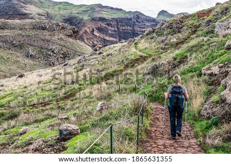 Girl hiking rocky cliffs clear near water of Atlantic Ocean bay Ponta de Sao Lourenco, the island of Madeira, Portugal Royalty-Free Stock Photo #1865631355