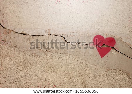 A heart painted on a cracked wall. The concept of broken heart, relationships, love, friendship, marriage, graffiti. Royalty-Free Stock Photo #1865636866