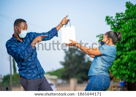 image of african man and woman, with face mask, holding a package-  delivery concept
