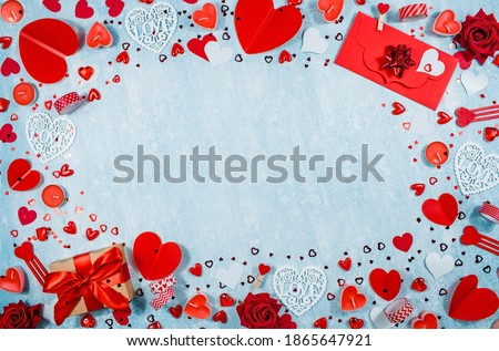 Greeting card for Valentine's Day. Red hearts, gift box, roses and candles on a blue background. Beautiful frame for text. Flatly. Copy the space. The concept of holiday and love. Royalty-Free Stock Photo #1865647921