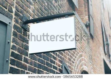 White blank signboard hanging on brick wall, mockup