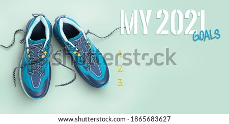 New year, new start business and health resolution concept for 2021. Top view of blue trainers on a blue background.