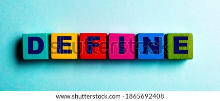 The word DEFINE is written on multicolored bright wooden cubes on a light blue background