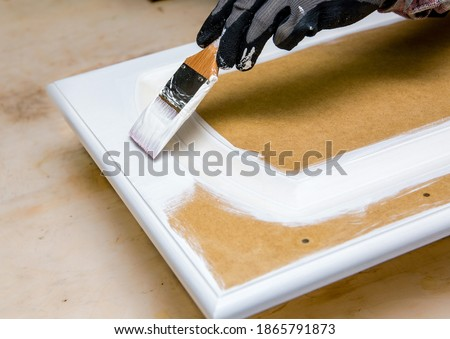 Repainting kitchen cabinet doors with white chalk paint indoors at home. Giving old kitchen new look concept. Hand holding a paint brush tool with paint against old cupboard door. Royalty-Free Stock Photo #1865791873