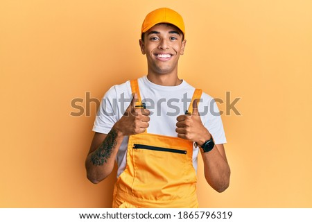 Young handsome african american man wearing handyman uniform over yellow background success sign doing positive gesture with hand, thumbs up smiling and happy. cheerful expression and winner gesture.