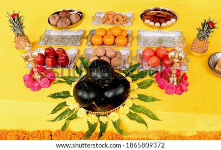 Long shot of all mix fruits on yellow background with manga leaves for pooja