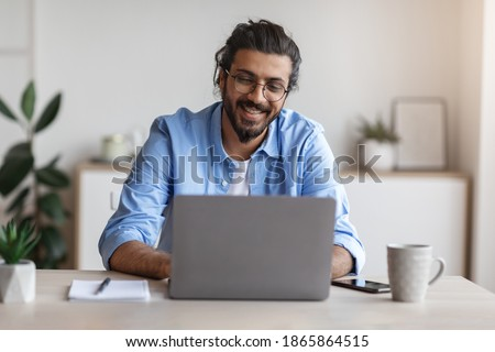 Freelance Work. Happy Millennial Indian Man Working On Computer At Home Office, Sitting At Desk With Laptop, Handsome Western Guy Looking At Device Screen And Smiling, Enjoying Remote Job, Copy Space Royalty-Free Stock Photo #1865864515