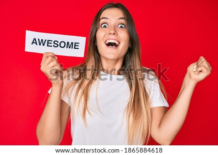Beautiful caucasian woman holding awesome banner screaming proud, celebrating victory and success very excited with raised arms  Royalty-Free Stock Photo #1865884618