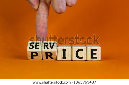 Service price symbol. Hand turns a cube and changes the words 'service' to 'price'. Beautiful orange background. Business and service price concept. Copy space. Royalty-Free Stock Photo #1865963407