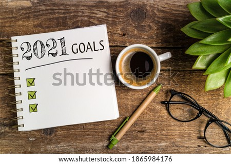 New year goals 2021 on desk. 2021 goals list with notebook, coffee cup, plant on wooden table. Resolutions, plan, goals, checklist, idea concept. New Year 2021 template, copy space #1865984176
