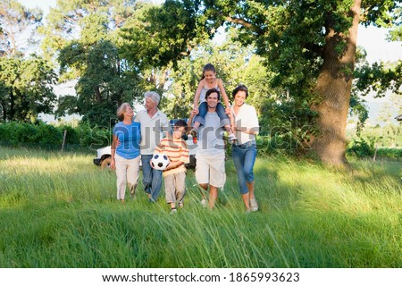 Horizontal shot of a multi-generational family walking in a woodland clearing with boy holding a soccer ball and his sister on dad's shoulder. Royalty-Free Stock Photo #1865993623