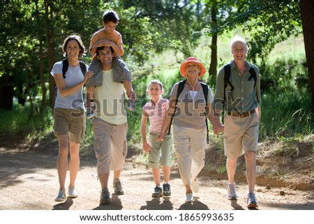 Horizontal shot of a multi-generational family with boy on the father's shoulder hiking on a mountain trail smile at the camera. Royalty-Free Stock Photo #1865993635