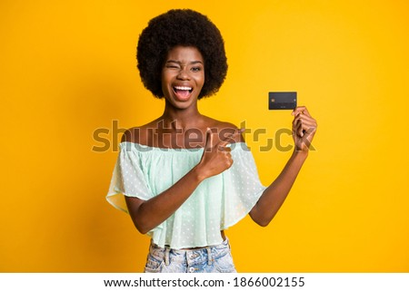 Photo portrait of winking girl pointing finger holding plastic card in one hand isolated on vivid yellow colored background