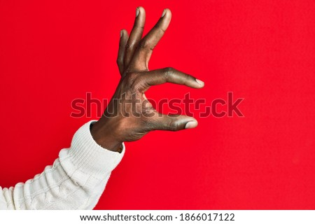 Arm and hand of african american black young man over red isolated background picking and taking invisible thing, holding object with fingers showing space  Royalty-Free Stock Photo #1866017122