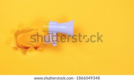 Woman hand arm hold megaphone isolated through torn yellow background Copy space advertisement place for text or image workspace mock up Hot news announce discounts sale hurry up communication concept Royalty-Free Stock Photo #1866049348