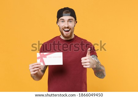 Excited young bearded tattooed man guy in casual t-shirt black cap posing isolated on yellow background studio. People lifestyle concept. Mock up copy space. Hold gift certificate, showing thumb up