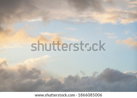 Clouds in the sky as a frame, sunset texture background. Blue, orange and yellow abstract shades. True high resolution photography
