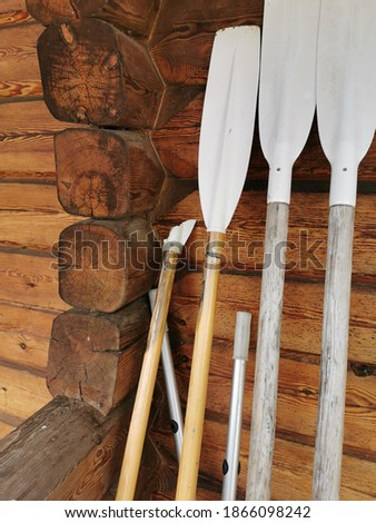 Paddles are placed against the wall. One oar is broken. Wooden house wall. Royalty-Free Stock Photo #1866098242