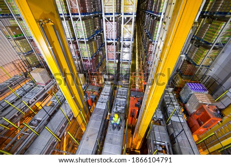 Wide shot of a worker standing below foodstuff merchandise stored in a warehouse with an automated storage and retrieval system  Royalty-Free Stock Photo #1866104791