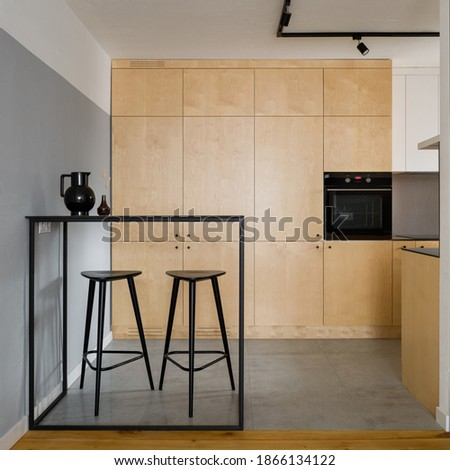 Modern, black table with tall bar stools in stylish kitchen with birch plywood cupboards Royalty-Free Stock Photo #1866134122