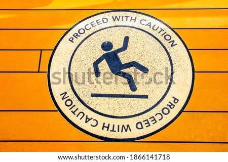 Proceed With Caution sign to alert of slippery floor showing symbol of person falling to the ground. Royalty-Free Stock Photo #1866141718