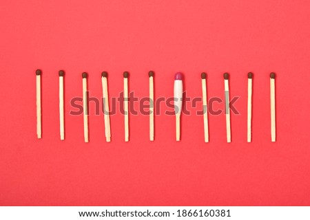 matches are arranged in a row on a red background, one waterproof match among simple matches top view Royalty-Free Stock Photo #1866160381