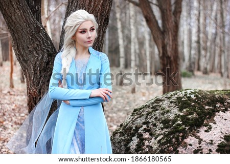 Young attractive girl with long blond hair in blue dress portrait in the park