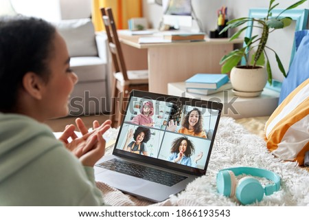 African teen girl talking with friends on distance video group conference call in bedroom. Mixed race teenager having fun chatting during virtual meeting at home communicating online lying in bed. #1866193543