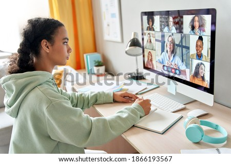 Mixed race teen school girl college student distance learning during virtual remote class, group online lesson on video conference call with teacher on computer screen studying at home by videocall. Royalty-Free Stock Photo #1866193567