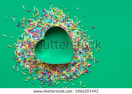 Coloured sprinkles with a heart-shaped cookie cutter on green paper background. Christmas love concept Royalty-Free Stock Photo #1866201442