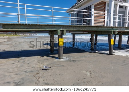 Wooden pier on thick piles on wet beach sand with a building on top of the boardwalk. There are blank yellow signs on the supports #1866245971
