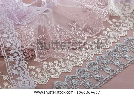 pile of beige, purple, white, gray gentle guipure, lace fabric on brown background. use for atelier. hygge champagne set sail concept. Royalty-Free Stock Photo #1866364639