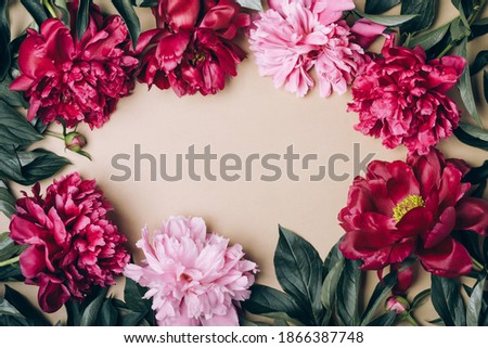 Beautiful peonies flowers frame on beige champagne background. Spring or summer floral background.