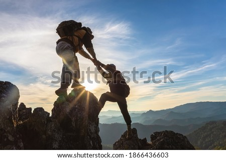 Silhouette Two Male hikers climbing up mountain cliff and one of them giving helping hand. People helping and, team work concept. Royalty-Free Stock Photo #1866436603
