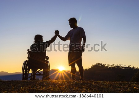 Silhouette of joyful disabled man in wheelchair raised hands with friend at sunset Royalty-Free Stock Photo #1866440101