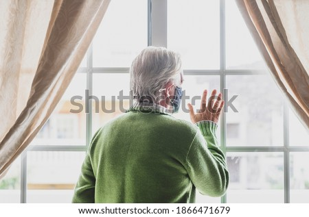 Coronavirus. Back view of a senior white haired man with green sweater in solitude at home behind the window, wearing a protective face mask due to coronavirus infection - elderly people in quarantine Royalty-Free Stock Photo #1866471679