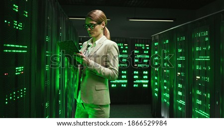 Caucasian woman standing at server with tablet device, tapping and checking processor. Female analytic in data storage working on digital security. African American male technician on background. Royalty-Free Stock Photo #1866529984