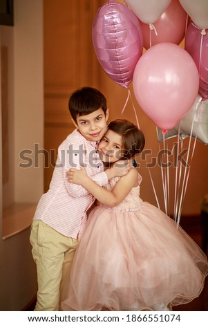 A boy and a girl are hugging each other. Balloons near children. A girl in a lush pink dress, and a boy in a pink shirt. Image with selective focus.