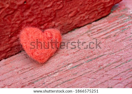 The red toy heart lies on the background of an old wooden surface. A symbol of love, loneliness, melancholy and depression. Royalty-Free Stock Photo #1866575251