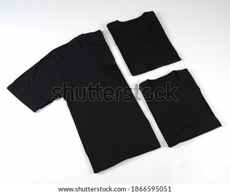 Black plain cotton shortsleeve crewneck t-shirt shot unfolded and folded in three different ways as a set isolated on white background. Three folded t-shirts. Converted in black and white.